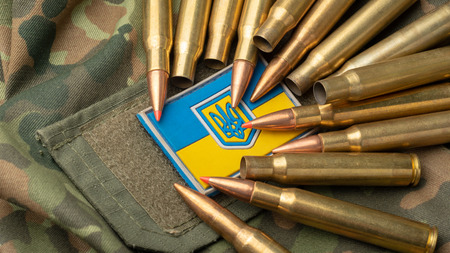 Ukrainian flag on the background of a camouflage military jacket and combat bullets. Country defense concept