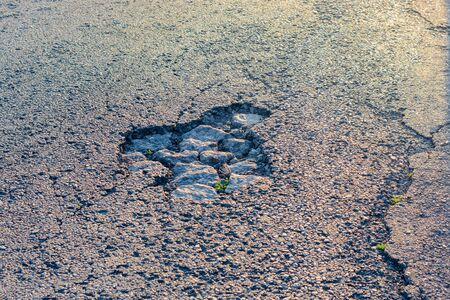 road pit close-up in the sun. Road repair concept. Background texture