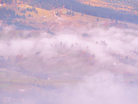 Carpatian village at mountains at the sunny foggy day