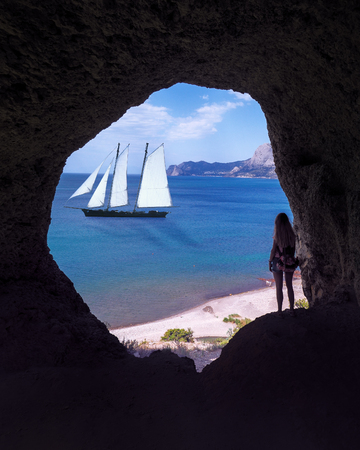 Girl at the cave at the mountains with sea view
