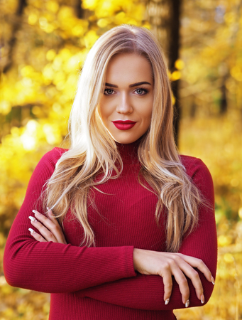 Blonde girl portrait at the autumn forest looking at camera
