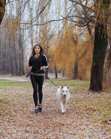 Young girl with dog running at the forest