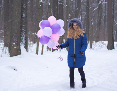 Young girl at blue coat with balloons at the forest