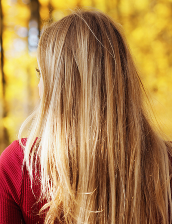 Blonde girl portrait at the autumn forest looking back view from back