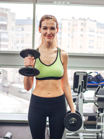 Young girl makes exercises at the gym