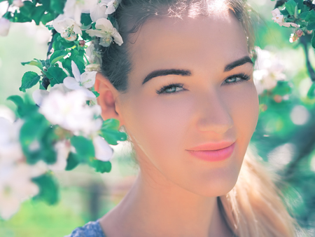 Portrait of young girl at the white spring flowers blossom