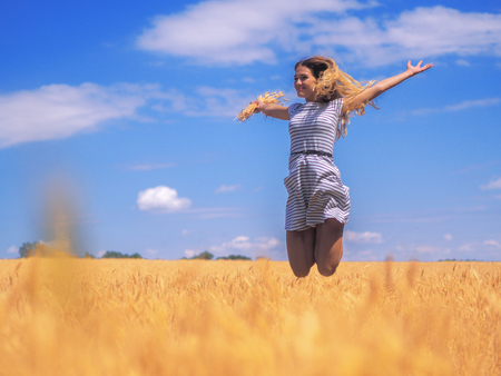 Young woman at the wheat field under the blue sky at the sunny day