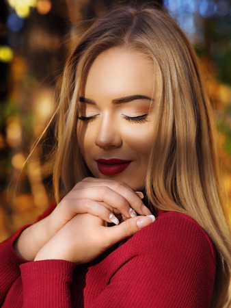Blonde girl portrait at the autumn forest with closed eyes