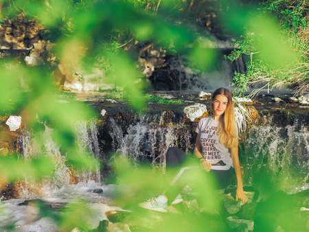 Young girl at the forest happy near waterfall