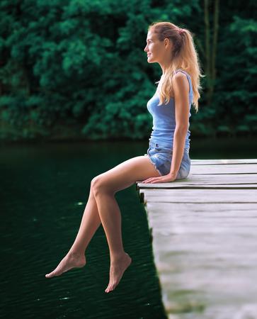 Girl sitting at the bridge at the lake
