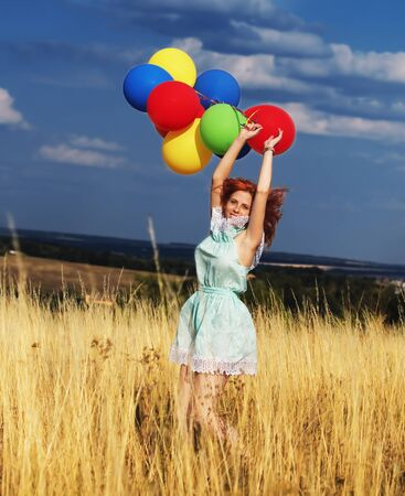 Girl redhead jumping with ballons at the yellow spikelets and blue sky
