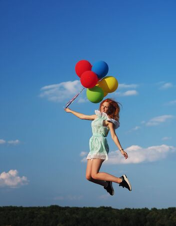 Young redhead girl with colorful balloons jumping at the blue sky