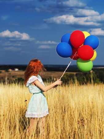 Girl redhead standing with ballons at the yellow spikelets and blue sky