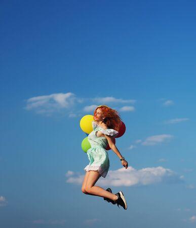 Giovane ragazza dai capelli rossi con palloncini colorati che saltano nel cielo blu