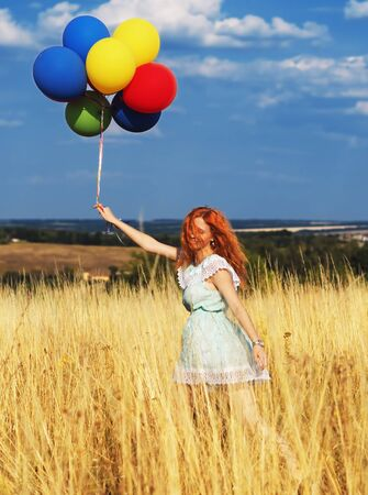 Girl redhead running with ballons at the yellow spikelets and blue sky
