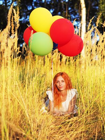 Girl redhead laying with ballons at the yellow spikelets