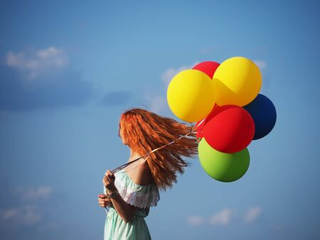 Young redhead girl with colorful balloons standing at the blue sky Reklamní fotografie