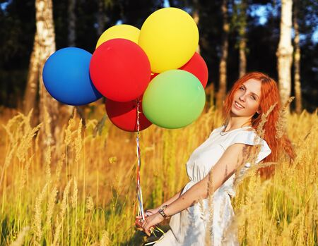 Girl redhead standing with ballons at the yellow spikelets Reklamní fotografie
