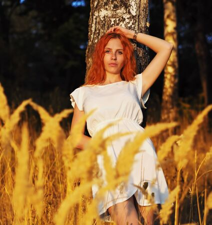 Girl redhead portrait at the yellow spikelets Reklamní fotografie