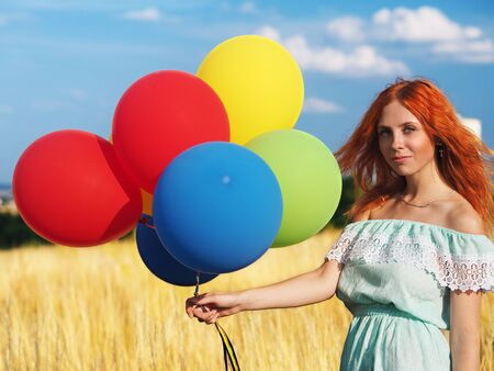 Young redhead girl with colorful balloons standing at the field