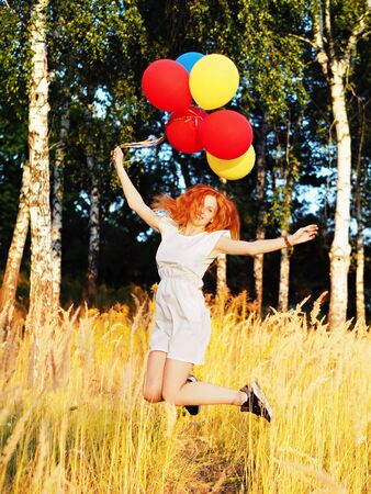 Girl redhead jumping with ballons at the yellow spikelets Reklamní fotografie