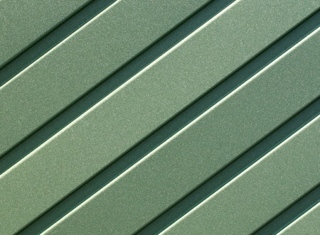 Green corrugated steel sheet with vertical guides.