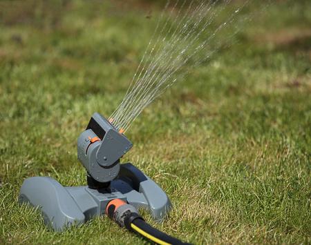paysagiste: Arroseur d'irrigation oscillant de la pelouse à midi Close-up
