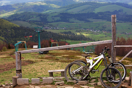 Carpathians. Two cyclists left mountain bikes for a respite. Ski lift in the background of a mountain landscape.