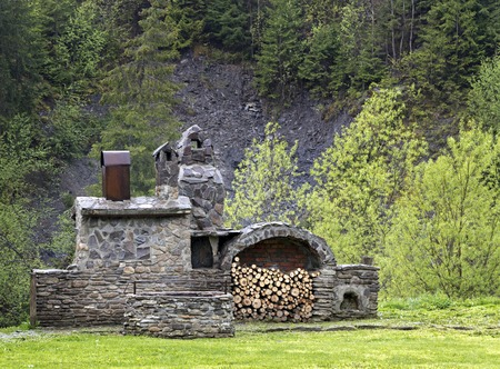 outdoor fireplace: Old stone stove with wood and smokehouse in the mountains