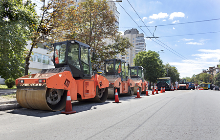 construction vibroroller: Among the summer noon three heavy road vibrating roller compactors and other equipment are ready for repair of the road in a modern city