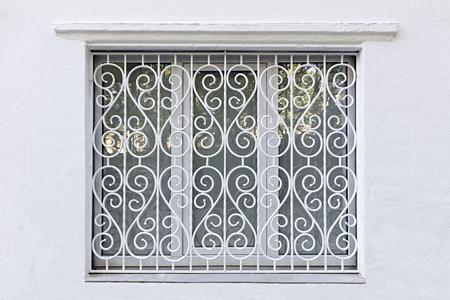 Janela na parede branca. Moldura figurada do orifício da janela. Treliça de ferro forjado encaracolado pintado de branco