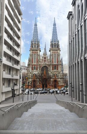 The facade of the Roman Catholic Cathedral of St. Nicholas in Kiev, the view of the cathedral between the high-rise buildings on the opposite side of the street. Stock Photo