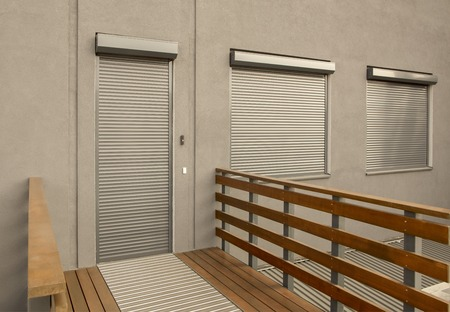 Light brown metal blinds on the doors and windows of the house