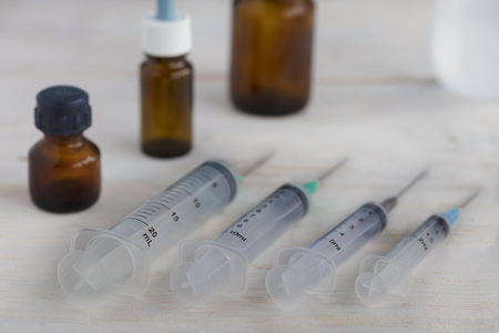 Medical syringes of various capacities and medical bottles lie diagonally on a white roughly painted wooden table.