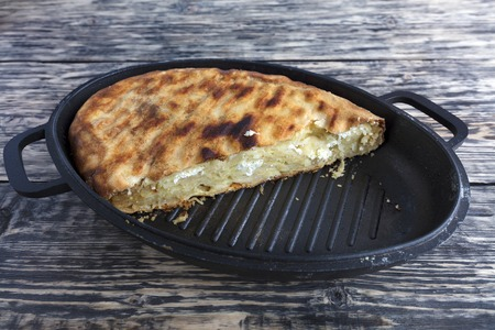 Homemade cake with cottage cheese and Parmesan cheese, which melted in a hot oven. Pie on a cast iron plate on an old wooden background.