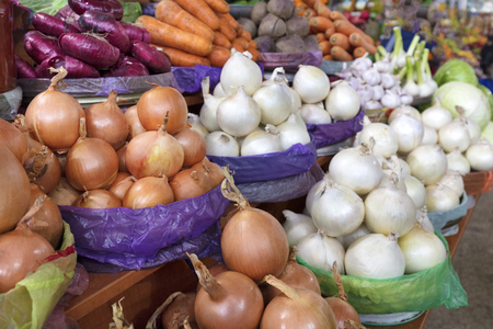 different varieties of onions and other vegetables for sale on the market Stock Photo