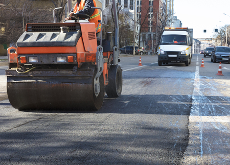 Heavy vibration roller compactor repairs the road on the asphalt surface on the road section of the roadway enclosed by road cones