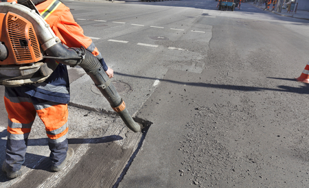 Worker with blower posing, cleaning out the dust with a leaf-blower for better asphalt adhesion.