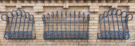 The fence of brickwork is decorated with a forged curly iron grating