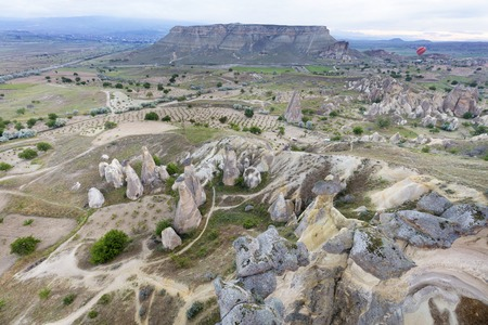 The mountains of Cappadocia impress with their nakedness and openness. Balloons rise above them.