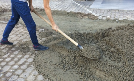 The worker level the foundation with mortar and shovel for repairing the sidewalk pavement tile