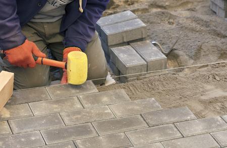 El trabajador coloca la losa del pavimento con martillos especiales, nivelando según el nivel del hilo tensado. Foto de archivo