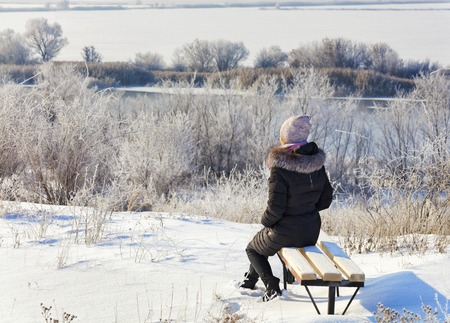 A young woman in the rays of the winter rising sun greets the dawn on the banks of the Southern Bug River, sits on a wooden bench and looks into the distance. Banque d'images