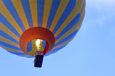 The flame of fire heats the air in a motley yellow-blue beautiful balloon and raises a basket of tourists to the blue sky, view from below. 免版税图像
