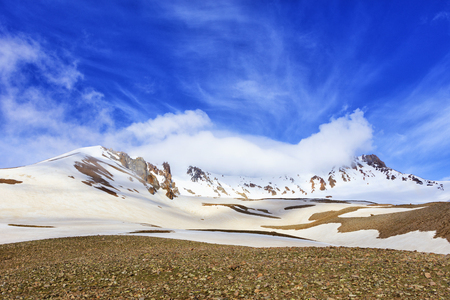 The snowy top of Mount Erciyis in central Turkey is shrouded in a white cloud against a bright blue sky on a sunny spring day Stock Photo