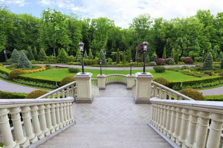 Stylish granite staircase with a balustrade with beautiful carved balusters in classic style, overlooks the beautiful lawn of a magnificent garden. Banque d'images