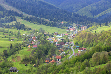 The winding road passes through a picturesque village between the mountains in the valley of the Carpathians.