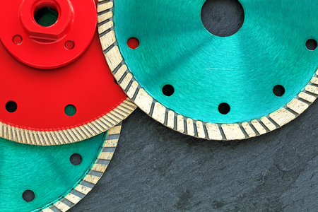 Several diamond cutting wheels of red and emerald color are located on top of each other against the background of gray granite close-up.