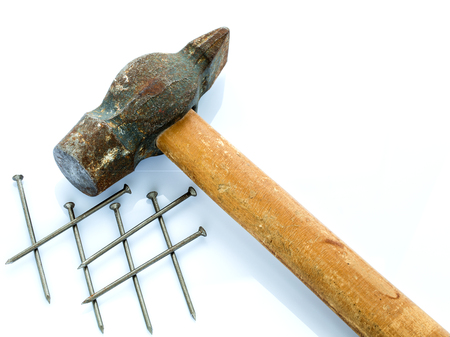 An old hammer with a wooden handle and a bunch of nails. Objects on a light background Stock Photo