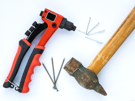 An old hammer with a wooden handle and a bunch of nails against new Rivet Gun and a bunch of Rivets Stock Photo